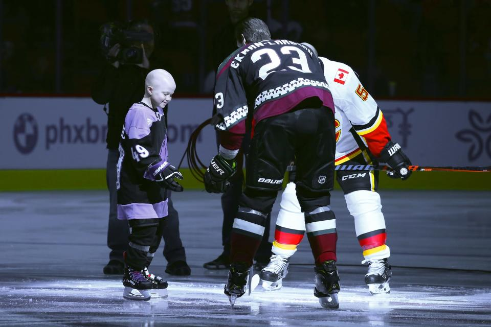 Leighton Accardo, left, who is battling cancer, drops the puck in front of Arizona Coyotes' Oliver Ekman-Larsson (23) and Calgary Flames' Mark Giordano (5) during an NHL Fights Cancer puck drop ceremony prior to an NHL hockey game in Glendale, Ariz., in this Saturday, Nov. 16, 2019, photo. Accardo's will to attack anything in her path, even terminal cancer, lifted an entire organization. The Arizona Coyotes will carry her spirit on by making her the first non-player, general manager or broadcaster to be inducted into an NHL team's ring of honor. (AP Photo/Ross D. Franklin)