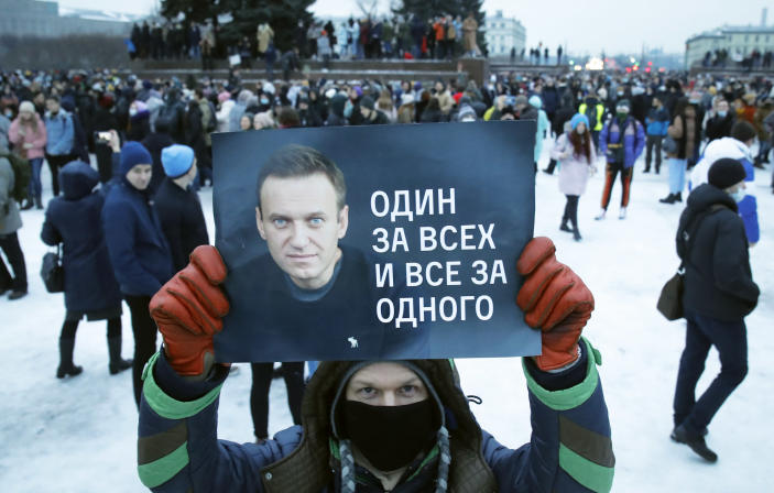 FILE - file photo, Jan. 23, 2021, a man holds a poster with a portrait Alexei Navalny and reads: 'One for all and all for one', during a protest rally against the jailing of opposition leader Alexei Navalny in St. Petersburg, Russia. Allies of Navalny are calling for new protests next weekend to demand his release, following a wave of demonstrations across the country that brought out tens of thousands in a defiant challenge to President Vladimir Putin. (AP Photo/Dmitri Lovetsky, File)