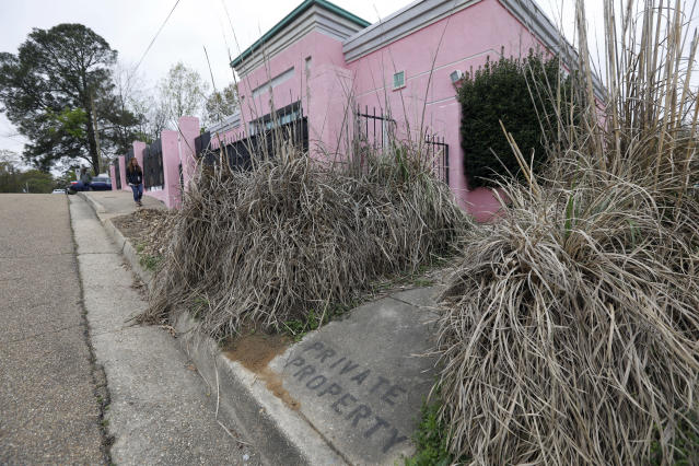 A private property sign and razor grass line some of the fencing outside the Jackson Women's Health Organization's clinic, the only facility in the state that performs abortions, Tuesday, March 20, 2018 in Jackson, Miss. A federal judge is temporarily blocking a new Mississippi law that bans abortion after 15 weeks, the most restrictive abortion law in the United States.(AP Photo/Rogelio V. Solis)