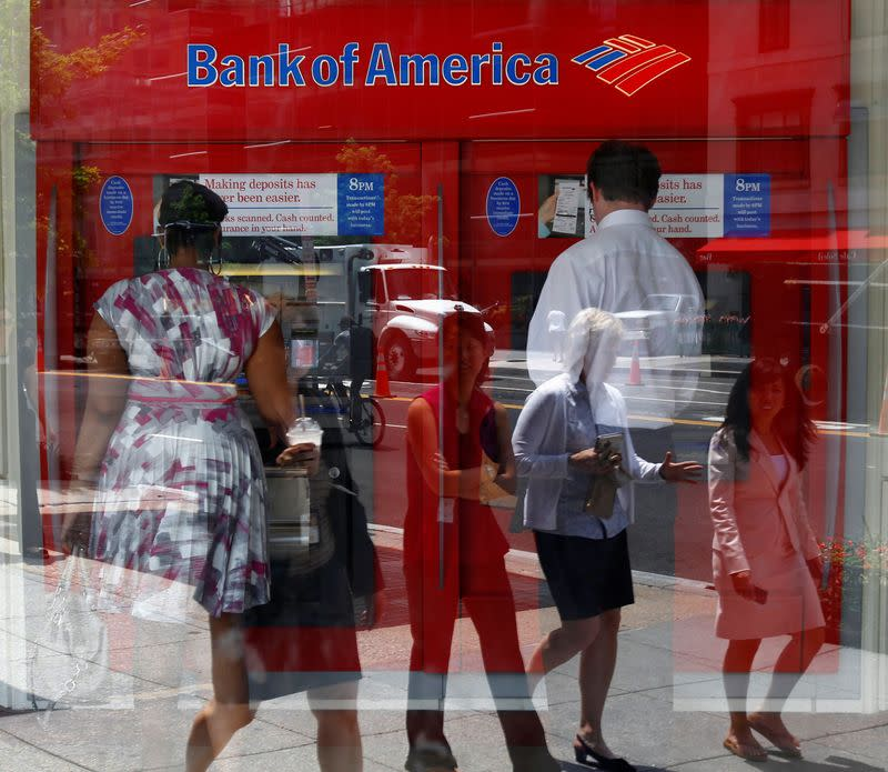 FILE PHOTO: Pedestrians are reflected in the window as customers conduct transactions at a Bank of America ATM in Washington