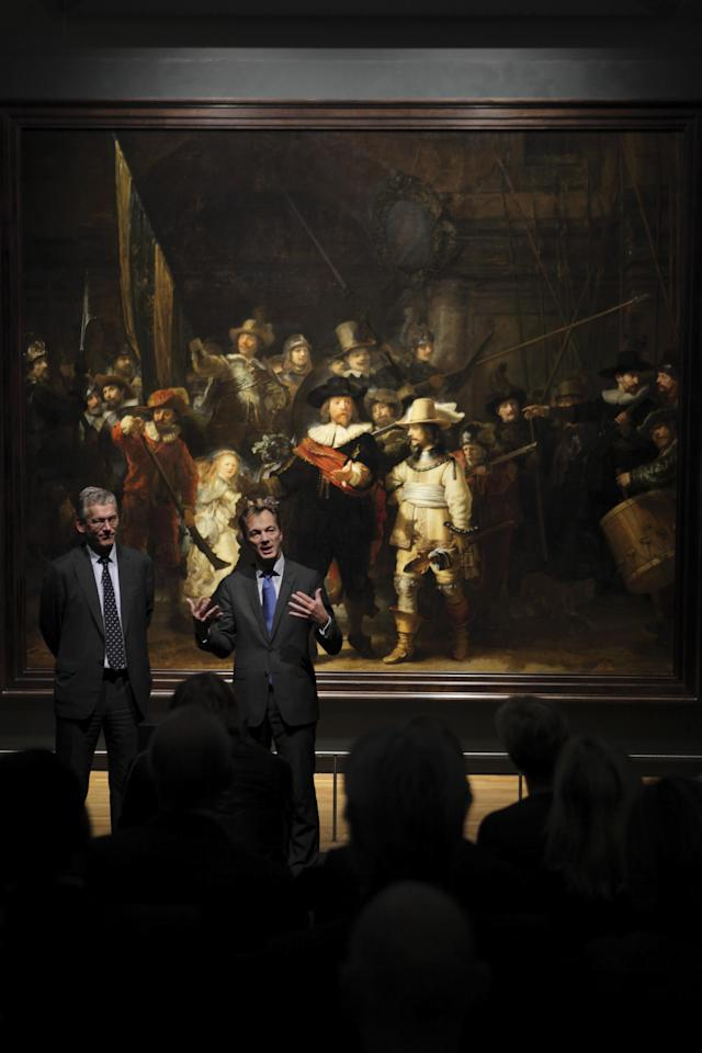 "Director Wim Pijbes of the national Rijksmuseum and Philips CEO Frans van Houten, left, answer questions in front of Rembrandt's ""Night Watch"", rear, in Amsterdam, Netherlands, Wednesday Oct. 26, 2011. The 1642 painting is officially titled ""The Company of Frans Banning Cocq."" Pijbes said Wednesday the painting, widely considered Rembrandt's greatest masterpiece, may in fact only have acquired the ""Night Watch"" name due to a dark varnish that was removed decades ago. He said the new LED lighting system custom designed by Philips mimics daylight, helping return the work to its original dynamic, colorful appearance. (AP Photo/Peter Dejong)"