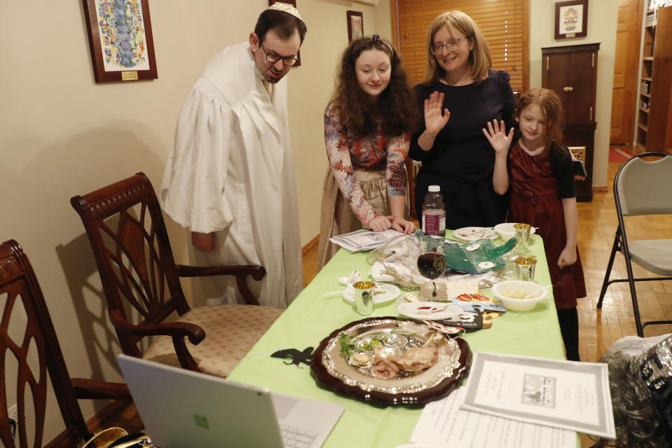 FILE - In this Wednesday, April 8, 2020 file photo, Rabbi Shlomo Segal, left, and his family wave goodbye to participants after he conducted a virtual Passover seder for members of his congregation, friends and family broadcast on YouTube from his home in the Sheepshead Bay neighborhood of Brooklyn during the current coronavirus outbreak in New York. From left, are Segal; daughter Shira, 12; wife, Adina, and daughter, Rayna, 8. In 2021, the Sabbath led directly into Passover, limiting the use of technology for Segal and his congregants. Instead of streaming their seder, the synagogue provided online workshops prior to Passover so families could do it on their own. Segal says that many of his members are still reluctant to gather together in person. (AP Photo/Kathy Willens)
