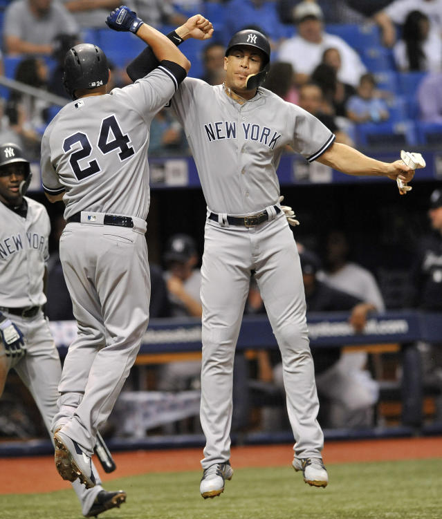 New York Yankees' Giancarlo Stanton celebrates with Gary Sanchez (24) after Sanchez hit a three-run home run off Tampa Bay Rays reliever Jalen Beeks during the third inning of a baseball game Tuesday, Sept. 25, 2018, in St. Petersburg, Fla. (AP Photo/Steve Nesius)