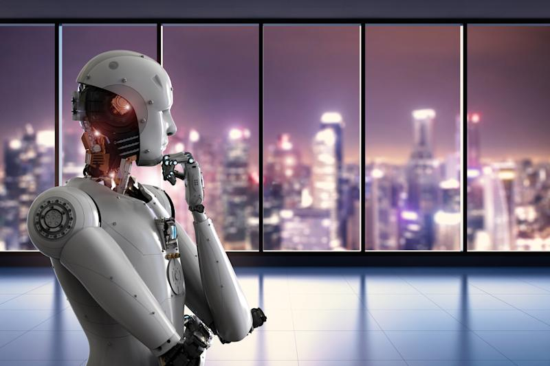 A robot looking out the window of a skyscraper.
