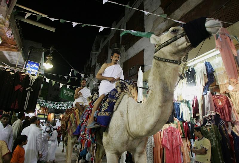 Saudi men, wearing traditional Islamic clothes for the Hajj, ride camels in the al-Alawi market in the old city of Jeddah, Saudi Arabia, January 3, 2006