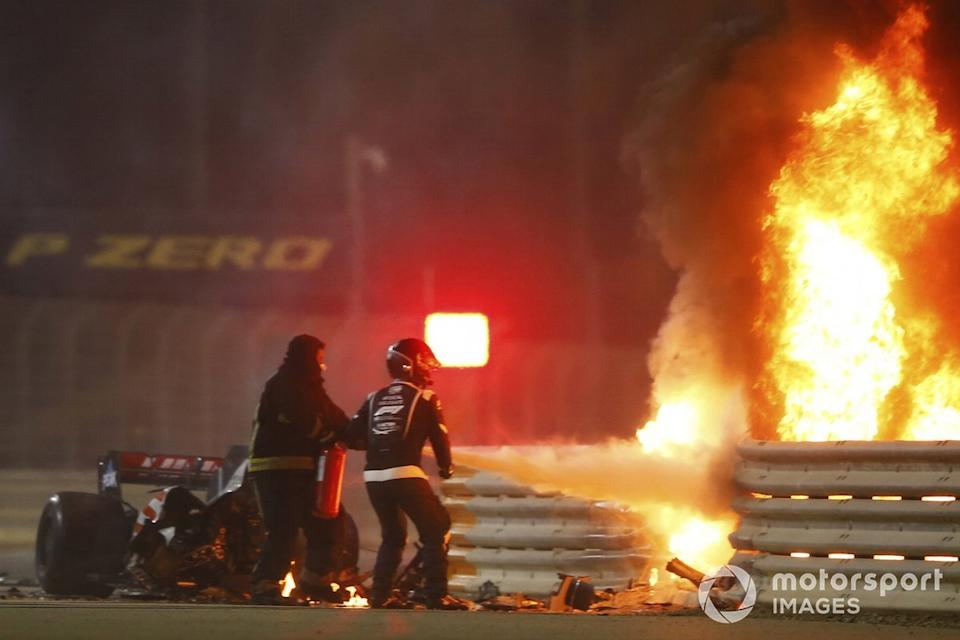 """Fire marshals use an extinguisher on a horrific accident of Romain Grosjean, Haas VF-20, on the opening lap of the Bahrain Grand Prix<span class=""""copyright"""">Andy Hone / Motorsport Images</span>"""