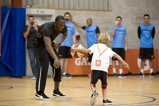 London Olympics champion Usain Bolt plays a one on one basketball game with Matthew Blackwell, 7, during a visit to the SkyCity Breakers at their training facility in Mairangi Bay, Auckland, New Zealand, Monday, Oct 8, 2012. The legendary Jamaican sprinter is making a short visit to New Zealand after holidaying in Australia. (AP Photo/New Zealand Herald, Dean Purcell) NEW ZEALAND OUT, AUSTRALIA OUT