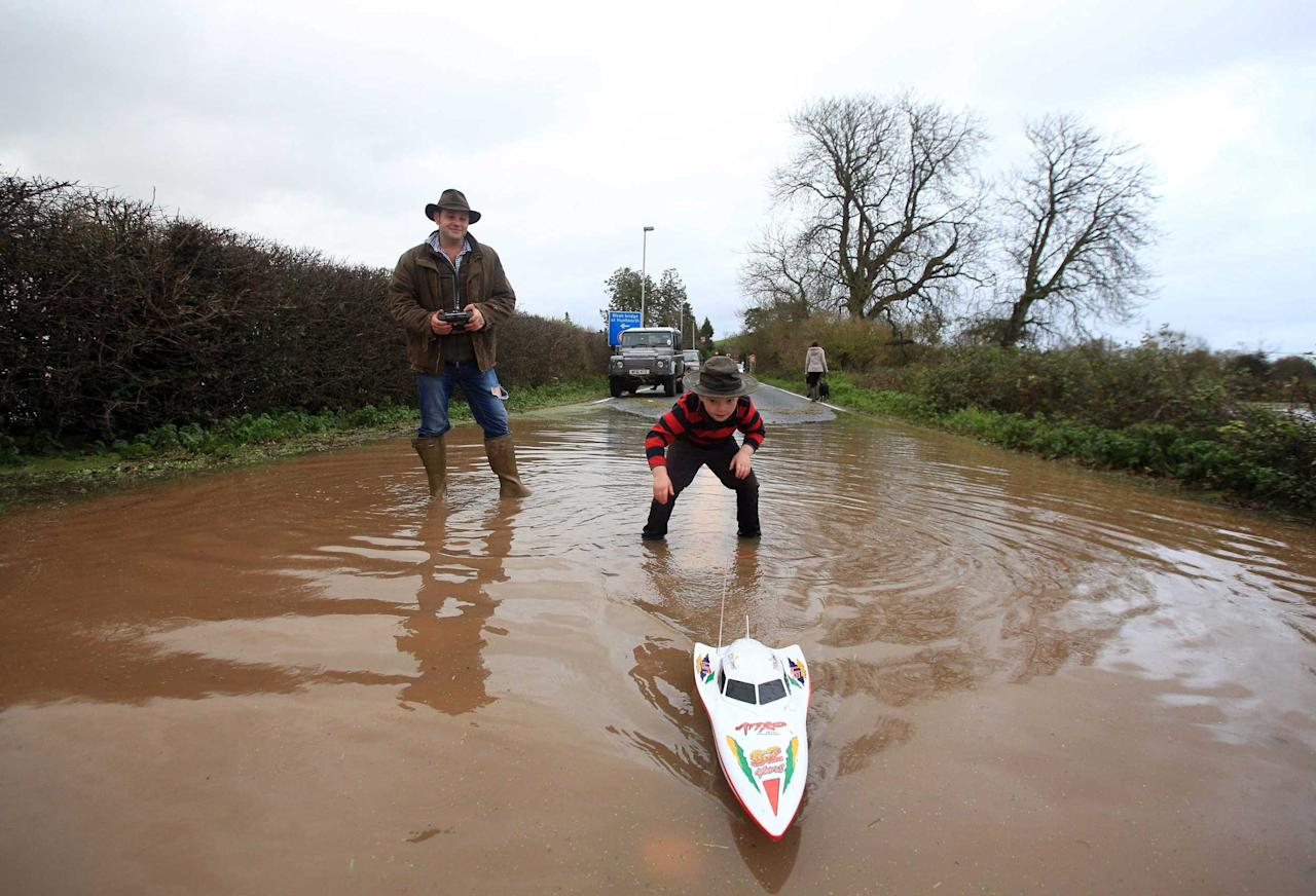 Sid Cowling and his son Mike play with a remote control toy boat on the flooded A361 just outside of Burrowbridge in Somerset (SWNS)