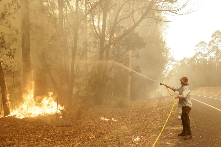 A man uses a water hose to battle a fire near Moruya, Australia, Saturday, Jan. 4, 2020. Australia's Prime Minister Scott Morrison called up about 3,000 reservists as the threat of wildfires escalated Saturday in at least three states with two more deaths, and strong winds and high temperatures were forecast to bring flames to populated areas including the suburbs of Sydney. (AP Photo/Rick Rycroft)