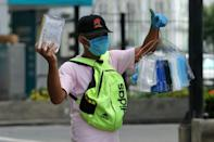 A man sells face masks to prevent the spread of the COVID-19 coronavirus, in north Guayaquil, Ecuador
