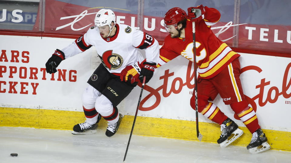 Ottawa Senators' Drake Batherson, left, and Calgary Flames' Rasmus Andersson chase the puck during second-period NHL hockey game action in Calgary, Alberta, Sunday, March 7, 2021. (Jeff McIntosh/The Canadian Press via AP)