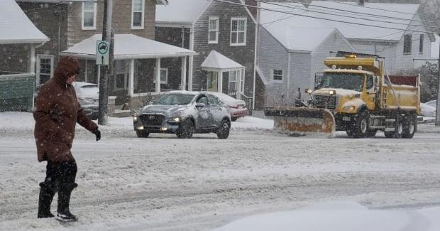A person walks along a snowy road in Halifax as a snowplow drives by during a late-winter storm. The storm caused crashes and cancellations. (Craig Paisley/CBC - image credit)