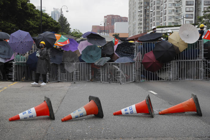 Protesters use umbrellas and steel barricades to block a road during a march through Sha Tin District in Hong Kong, Sunday, July 14, 2019. Opponents of a proposed Hong Kong extradition law have begun a protest march, adding to an outpouring of complaints the territory's pro-Beijing government is eroding its freedoms and autonomy. (AP Photo/Kin Cheung)