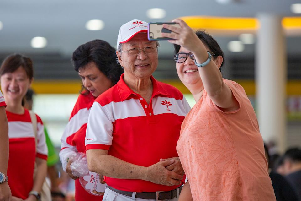 """A woman takes a selfie with Progress Singapore Party chief Tan Cheng Bock during the party's walkabout at the Tiong Bahru Market hawker centre on 29 September. Read our story: <a href=""""https://bit.ly/2rE9Dw9"""" rel=""""nofollow noopener"""" target=""""_blank"""" data-ylk=""""slk:https://bit.ly/2rE9Dw9"""" class=""""link rapid-noclick-resp"""">https://bit.ly/2rE9Dw9</a> (PHOTO: Dhany Osman / Yahoo News Singapore)"""