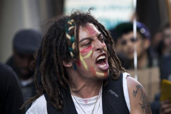 """An Occupy Wall Street protester shouts while marching through the streets of the Financial District during a """"Spring Training"""" exercise in New York April 6, 2012. Organizers say the training is meant to teach people how to protest, avoid law enforcement and stay safe."""