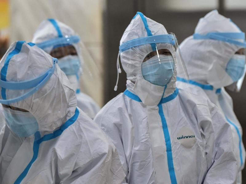 Medical staff members wearing protective clothing to help stop the spread of a deadly virus: AFP via Getty Images