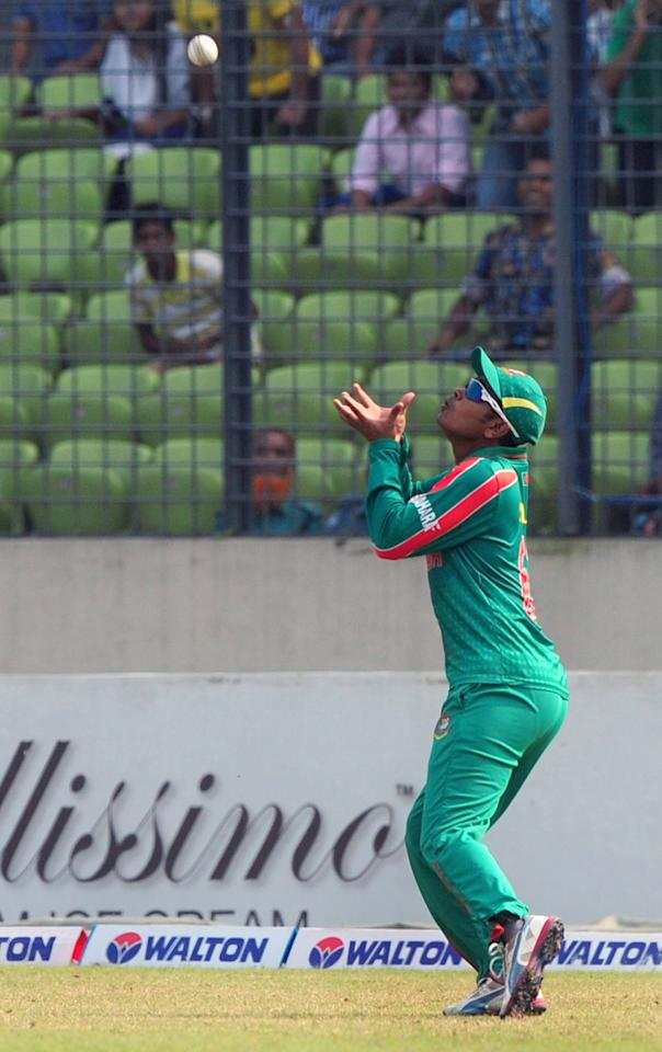 Bangladesh cricketer Shamsur Rahman takes the catch for the wicket of New Zealand batsman Anton Devcich during the T20 match between Bangladesh and Zew Zealand at the Sher-e-Bangla National Cricket Stadium in Dhaka on November 6, 2013. AFP PHOTO/ Munir uz ZAMAN        (Photo credit should read MUNIR UZ ZAMAN/AFP/Getty Images)