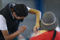 FILE - In this Feb. 24, 2021, file photo, a medical worker injects a woman with a dose of the Russian COVID-19 vaccine Sputnik V at the Palacio de los Deportes, in the Iztacalco borough of Mexico City. Russia's boast in August that it was the first country to authorize a coronavirus vaccine led to skepticism because of its insufficient testing on only a few dozen people. Now, with demand growing for the Sputnik V, experts are raising questions again, this time over whether Moscow can keep up with all the orders from countries that want it. (AP Photo/Rebecca Blackwell, File)