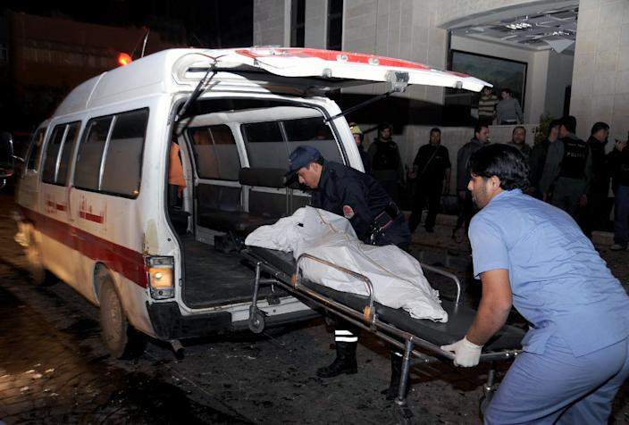 In this Wednesday, Dec. 12, 2012 photo released by the Syrian official news agency SANA, a paramedic and policeman carry a body into an ambulance after explosions hit the main gate of the Syrian Interior Ministry in Damascus, Syria. Three bombs collapsed walls in the Syrian Interior Ministry building Wednesday in Damascus, killing several, as rebels fighting to overthrow President Bashar Assad edged closer to the capital, the symbol of his power. (AP Photo/SANA)