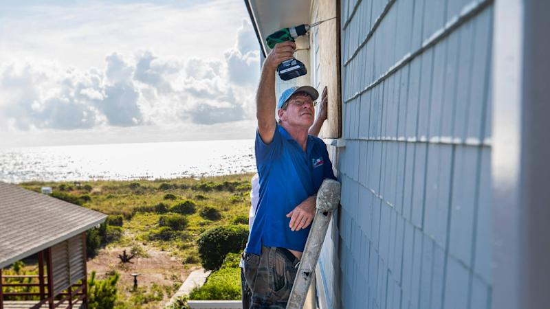Mandatory Credit: Photo by JIM LO SCALZO/EPA-EFE/REX/Shutterstock (9880068t)Butch Beaudry drills a wooden plank over the window of an oceanfront home, less than two days before Hurricane Florence is expected to strike Wrightsville Beach, North Carolina, USA, 12 September 2018.