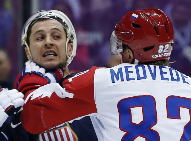 Russia defenseman Yevgeni Medvedev grabs USA forward Ryan Callahan by the neck in the first period of a men's ice hockey game at the 2014 Winter Olympics, Saturday, Feb. 15, 2014, in Sochi, Russia. (AP Photo/Julio Cortez)