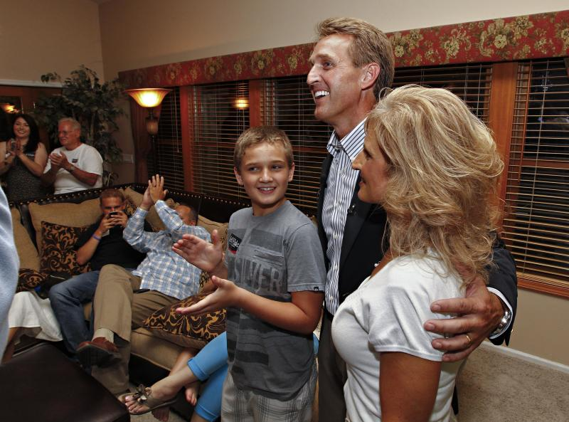 Arizona Republican Senate candidate and current U.S. Rep. Jeff Flake, R-Ariz., speaks at a primary election night party with is wife, Cheryl and son, Tanner, Tuesday, Aug. 28, 2012, at his home in Mesa, Ariz. Early polling numbers have Flake ahead of his challenger, Wil Cardon,in his effort to fill retiring Sen. Jon Kyl's, R-Ariz, seat. (AP Photo/Matt York)