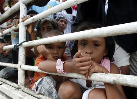 Children riding in a truck with other people made homeless by Super Typhoon Haiyan, look out of the vehicle as they wait to get relief goods at a government centre in Bogo, Cebu in the central Philippines November 17, 2013. REUTERS/Erik De Castro