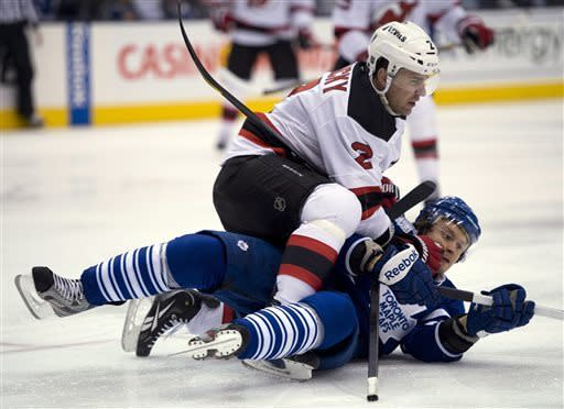 Toronto Maple Leafs center Mikahail Grabovski, bottom, and New Jersey Devils defenseman Marke Zidlicky tumble during the second period of their NHL hockey game in Toronto, Monday, April 15, 2013. (AP Photo/The Canadian Press, Frank Gunn)