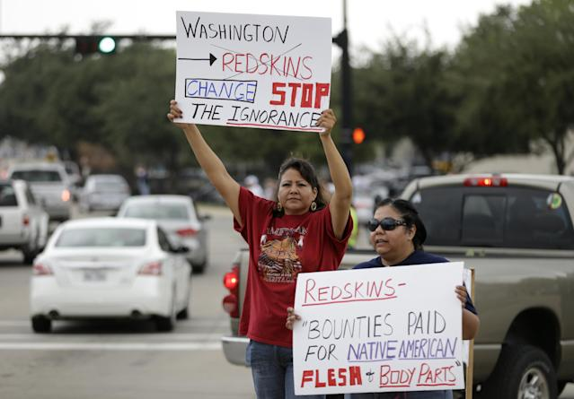 Yolanda Blue Horse, left, and Diana Parton, right, a member of the Caddo Nation, protest with others before an NFL football game between the Dallas Cowboys and Washington Redskins, Sunday, October 13, 2013, in Arlington, Texas. (AP Photo/LM Otero)