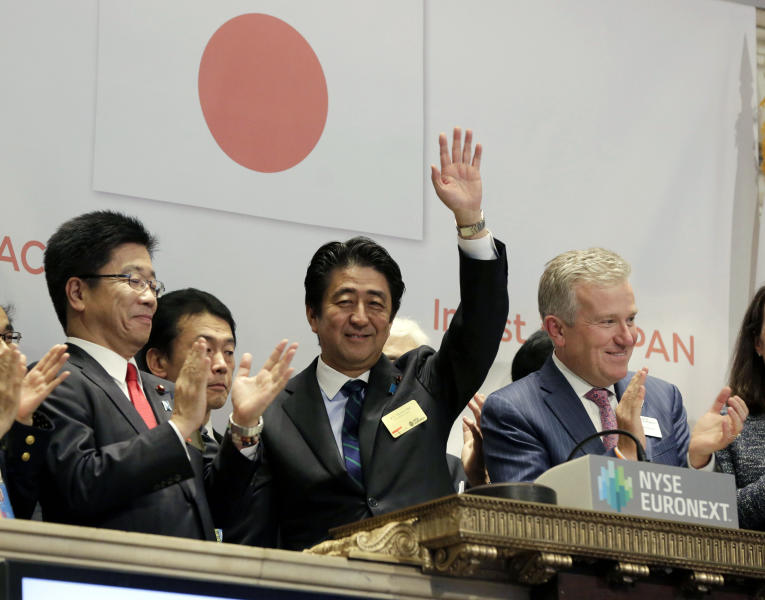 Japan's Prime Minister Shinzo Abe, center, waves after ringing the closing bell, with NYSE CEO Duncan Niederauer, right, at the New York Stock Exchange, Wednesday, Sept. 25, 2013. (AP Photo/Richard Drew)