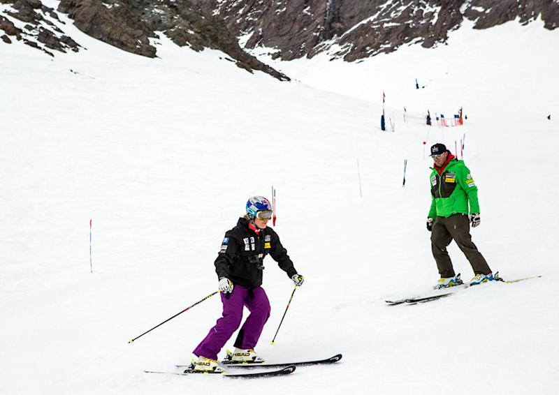 In this Aug. 31, 2013 photo provided by Red Bull, Lindsey Vonn, foreground, works with U.S. ski team coach Jeff Fergus in Portillo, Chile. The four-time World Cup overall champion returned to the slopes over the weekend nearly seven months after her injury. She eased her way back with two gentle and relaxed training runs. (AP Photo/Red Bull, Jonathan Selkowitz)