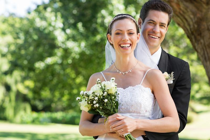 Smiling bride with bouquet of flowers standing in front of groom outdoors