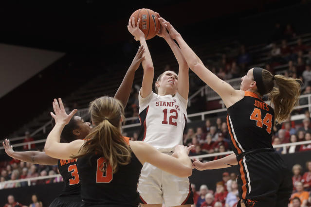 Stanford guard Lexie Hull (12) shoots between Oregon State guard Madison Washington, left, guard Mikayla Pivec (0) and forward Taylor Jones (44) during the second half of an NCAA college basketball game in Stanford, Calif., Friday, Feb. 21, 2020. (AP Photo/Jeff Chiu)
