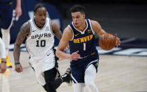 Denver Nuggets forward Michael Porter Jr., right, collects the ball as San Antonio Spurs forward DeMar DeRozan defends in the second half of an NBA basketball game Friday, April 9, 2021, in Denver. (AP Photo/David Zalubowski)