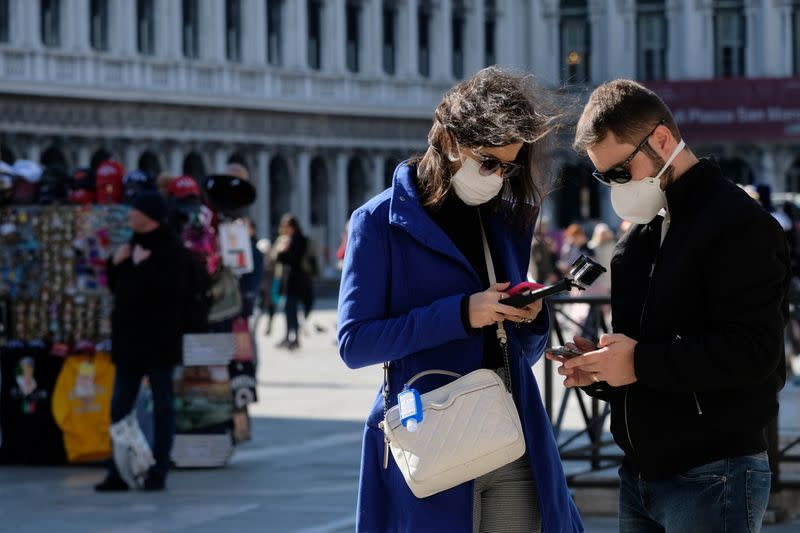 Tourists wear protective masks in Saint Mark's Square in Venice as Italy battles a coronavirus outbreak