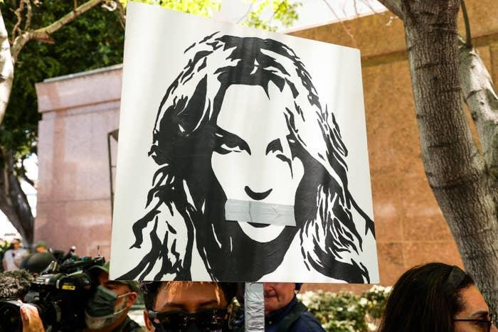 A protester holding up a sign with an image of Britney with tape over her mouth