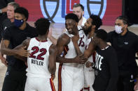 Miami Heat's Jimmy Butler (22), Bam Adebayo, center, Derrick Jones Jr., center right, and others celebrate with overtime win in an NBA conference final playoff basketball game against the Boston Celtics on Tuesday, Sept. 15, 2020, in Lake Buena Vista, Fla. (AP Photo/Mark J. Terrill)