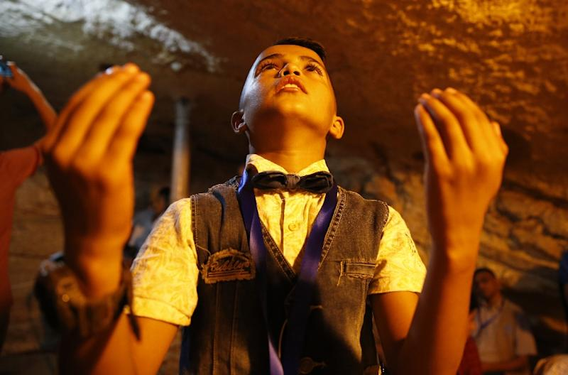 A Palestinian boy from Gaza prays inside the Dome of the Rock mosque in Jerusalem's Al-Aqsa mosque compound on August 20, 2017 (AFP Photo/AHMAD GHARABLI)