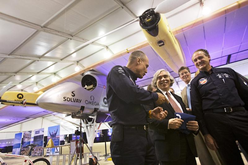 Energy Secretary Ernest Moniz, center, talk with Bertrand Piccard, left, and Andre Borschberg, the pilots of the Solar Impulse plane, in front of the purely solar powered plane during a media availability at the Smithsonian National Air and Space Museum's Steven F. Udvar-Hazy Center at Dulles International Airport in Chantilly, Va., Monday, June 17, 2013. The solar-powered plane nearing the close of a cross-continental journey landed at Dulles early Sunday, only one short leg to New York remaining on a voyage that opened in May. (AP Photo/Jacquelyn Martin)