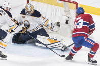 Montreal Canadiens' Max Domi (13) moves in on Buffalo Sabres goaltender Carter Hutton as Sabres' Rasmus Ristolainen defends during second period NHL hockey action in Montreal, Saturday, March 23, 2019. (Graham Hughes/The Canadian Press via AP)