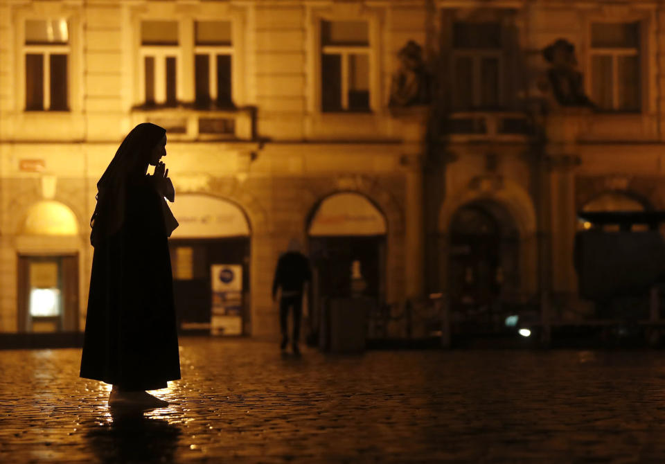 A nun prays on the near empty Old Town Square in Prague, Czech Republic, Friday, Oct. 23, 2020. (AP Photo/Petr David Josek)
