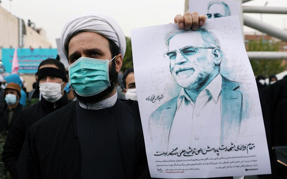 A protester holds a picture of Mohsen Fakhrizadeh, Iran's top nuclear scientist, during a demonstration against his killing in Tehran in November  - WANA/Reuters