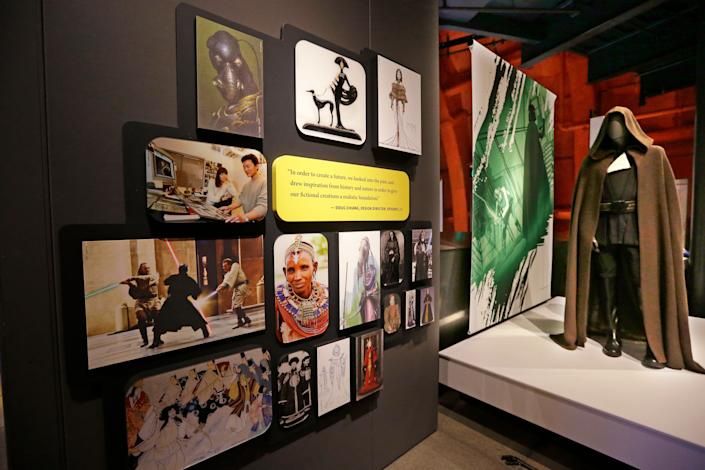 A photographic display near a Jedi robe gives information about cultural influences on Star Wars costumes. (AP Photo/Elaine Thompson)