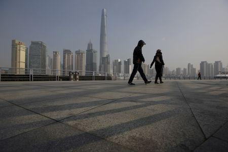 People walk in front of the financial district of Pudong in Shanghai, China, January 19, 2016. REUTERS/Aly Song