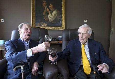 The world's oldest living twin brothers, Paulus (L) and Pieter Langerock from Belgium, 102, toast while sitting in their living room at the Ter Venne care home in Sint-Martens-Latem, Belgium, August 11, 2015. REUTERS/Yves Herman