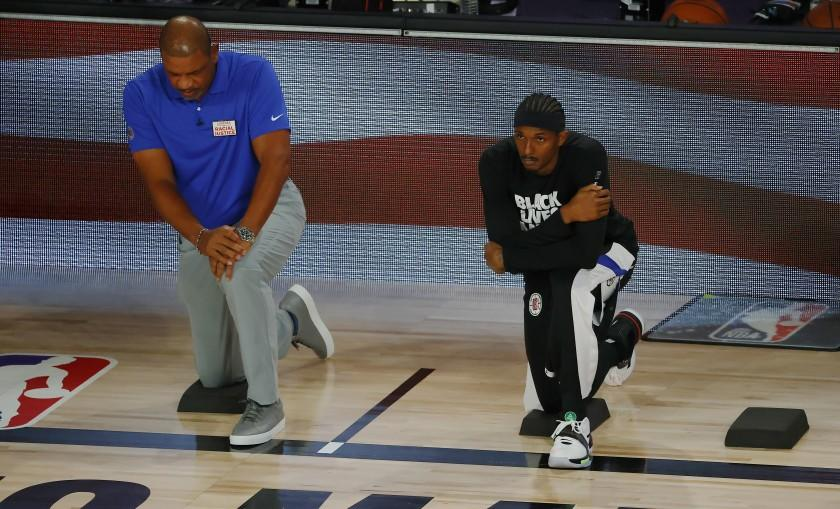 Los Angeles Clippers' Lou Williams, right, and head coach Doc Rivers look on during the national anthem.