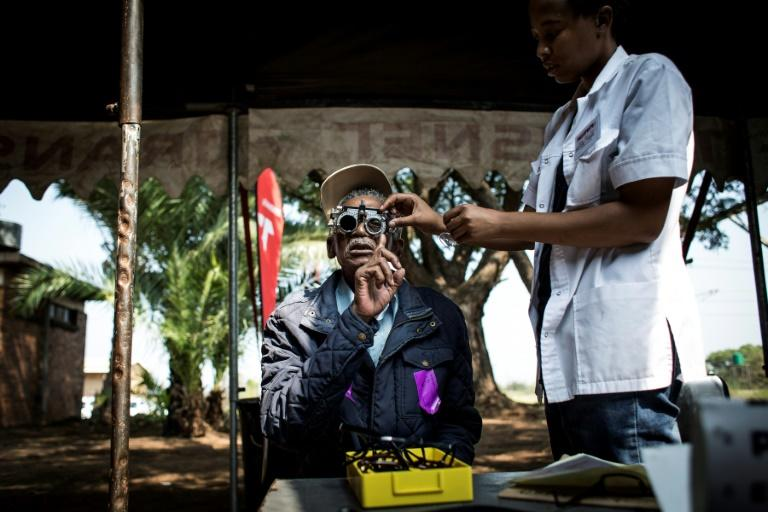 A man getting his eyes tested outside the Phelophepa train, whose services include low-cost glasses