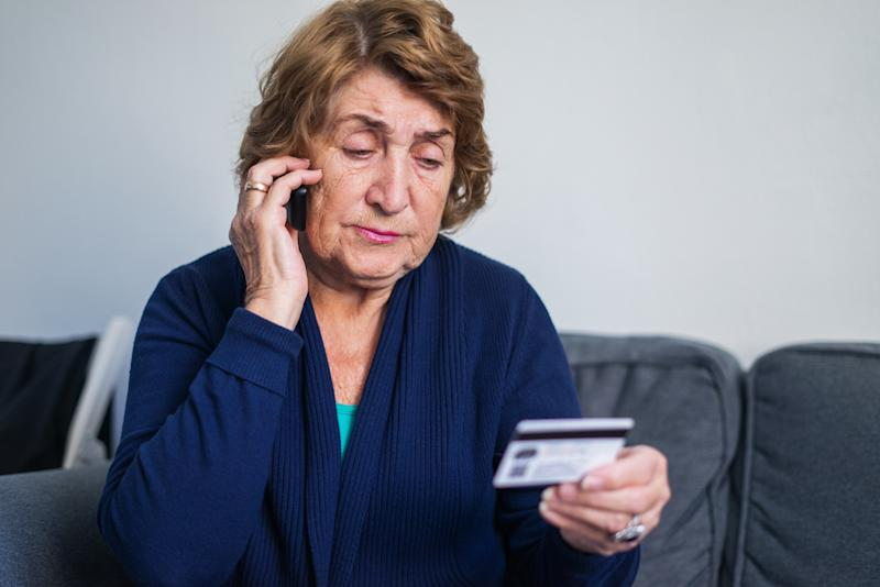 Senior woman using mobile phone while holding credit card