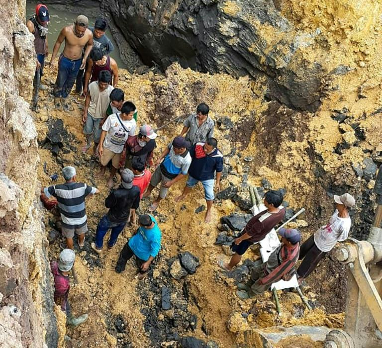 Villagers try to evacuate workers trapped 20 metres underground at an unlicensed coal mine in Muara Enim regency, South Sumatra, Indonesia