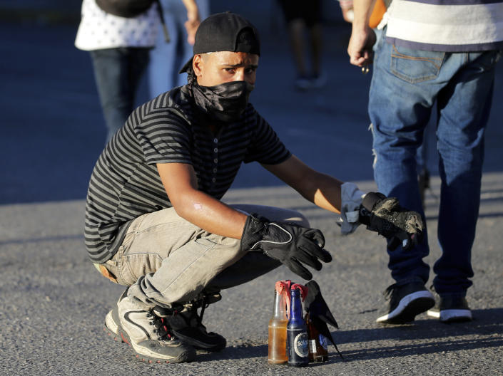 An anti-government protester readies gasoline bombs during clashes against the Venezuelan Bolivarian National Guard, after a rally demanding the resignation of President Nicolas Maduro in Caracas, Venezuela, Wednesday, Jan. 23, 2019. The head of Venezuela's opposition-run congress declared himself interim president at the rally, until new elections can be called.(AP Photo/Fernando Llano)